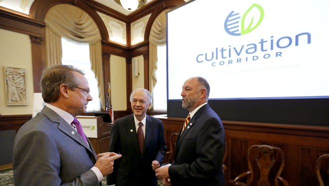 From left, Paul Schickler, president of DuPont Pioneer and Capital Corridor co-chairmen Steve Zumbach and Steven Leath visit following a ceremony introducing Cultivation Corridor Monday, April 21, 2014 in Des Moines.