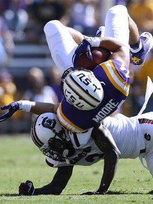 LSU fullback John David Moore, top, is tackled by South Carolina cornerback Chris Lammons during the first half of a game last month.