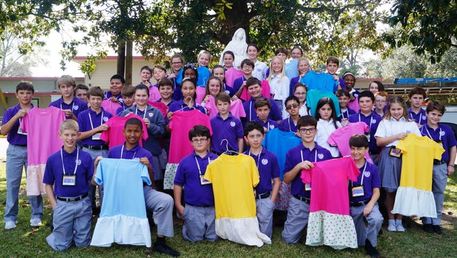 "Opelousas Catholic students have been carrying out their ""Service above Self"" motto. Sixth graders in Judi Lucito's religion classes recently completed a special project of sewing tee-shirt dresses for underprivileged children in other countries. With the help of volunteer mothers and grandmothers in the classroom, the students gathered and sewed skirts onto tee-shirts. For many, it was a first-time experience at a sewing machine. With pride in their work, the students came together to display their finished products before the dresses were shipped out."
