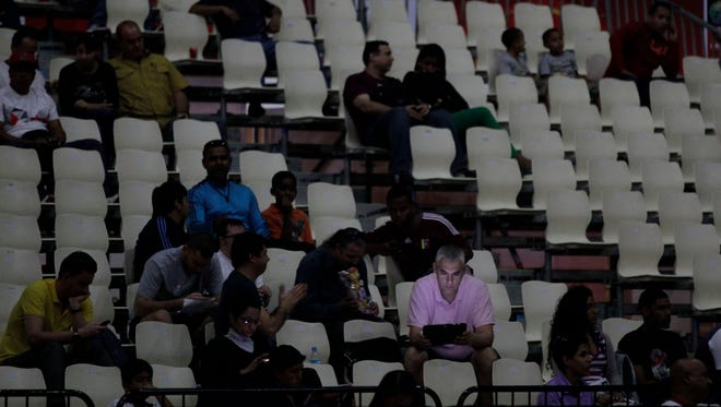 A fan looks at his laptop as he waits for play to resume at a FIBA World Cup qualifying basketball game during a power outage in Caracas on Sept. 3. The massive blackout  generated estimated losses of up to $1 billion to the economy.