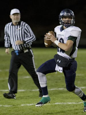 Damonte Ranch Mustangs quarterback Cade McNamara rolls out against Galena Grizzlies as referee James Hansen watches during their football game played on  October 29, 2015 in Reno.