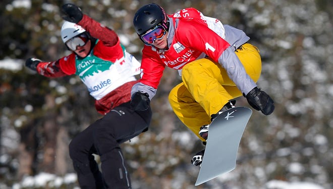 Lindsey Jacobellis flies through the air in front of Maelle Ricker in the women's semi-finals at the FIS Snowboard Cross World Cup in Lake Louise, Alberta, Canada.