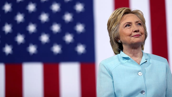 Hillary Clinton looks on as her running mate, Tim Kaine, speaks during a campaign rally at Florida International University Panther Arena on July 23, 2016, in Miami.