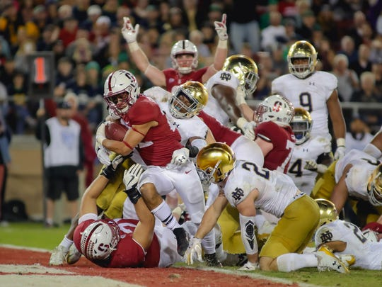 Stanford running back Cameron Scarlett (22) runs in for a touchdown against Notre Dame Fighting Irish linebacker Nyles Morgan (5) during the fourth quarter at Stanford Stadium last season.
