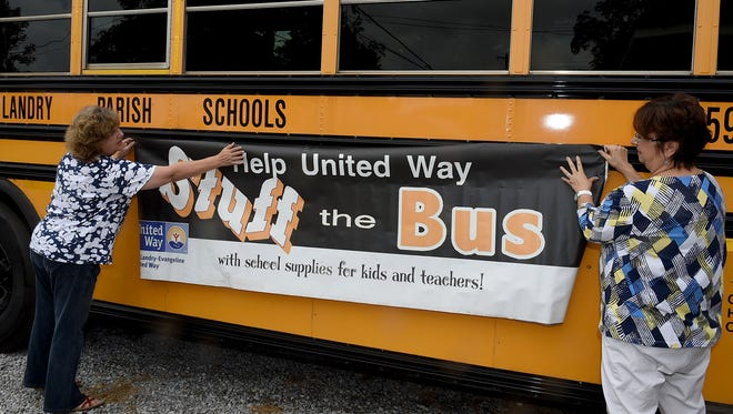 St. Landry/Evagelne United Way representatives Angela Guidry, left, and Ginger LeCompte,  post a Stuff the Bus sign onto a St. Landry Parish School Board bus parked at United Way offices Friday morning.
