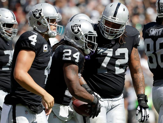 Oakland Raiders running back Marshawn Lynch (24) is congratulated by quarterback Derek Carr (4) and tackle Donald Penn (72) after scoring a touchdown against the New York Jets during the first half of an NFL football game in Oakland, Calif., Sunday, Sept. 17, 2017. (AP Photo/Marcio Jose Sanchez)
