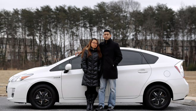 In this Feb. 14, 2015 picture, Eri and John Castro pose in front of their 2011 Toyota Prius in Glen Burnie, Md. The Castros bought the pre-owned car last year, only to find out after they got it home that it was under recall because it could stall without warning. (AP Photo/Patrick Semansky)