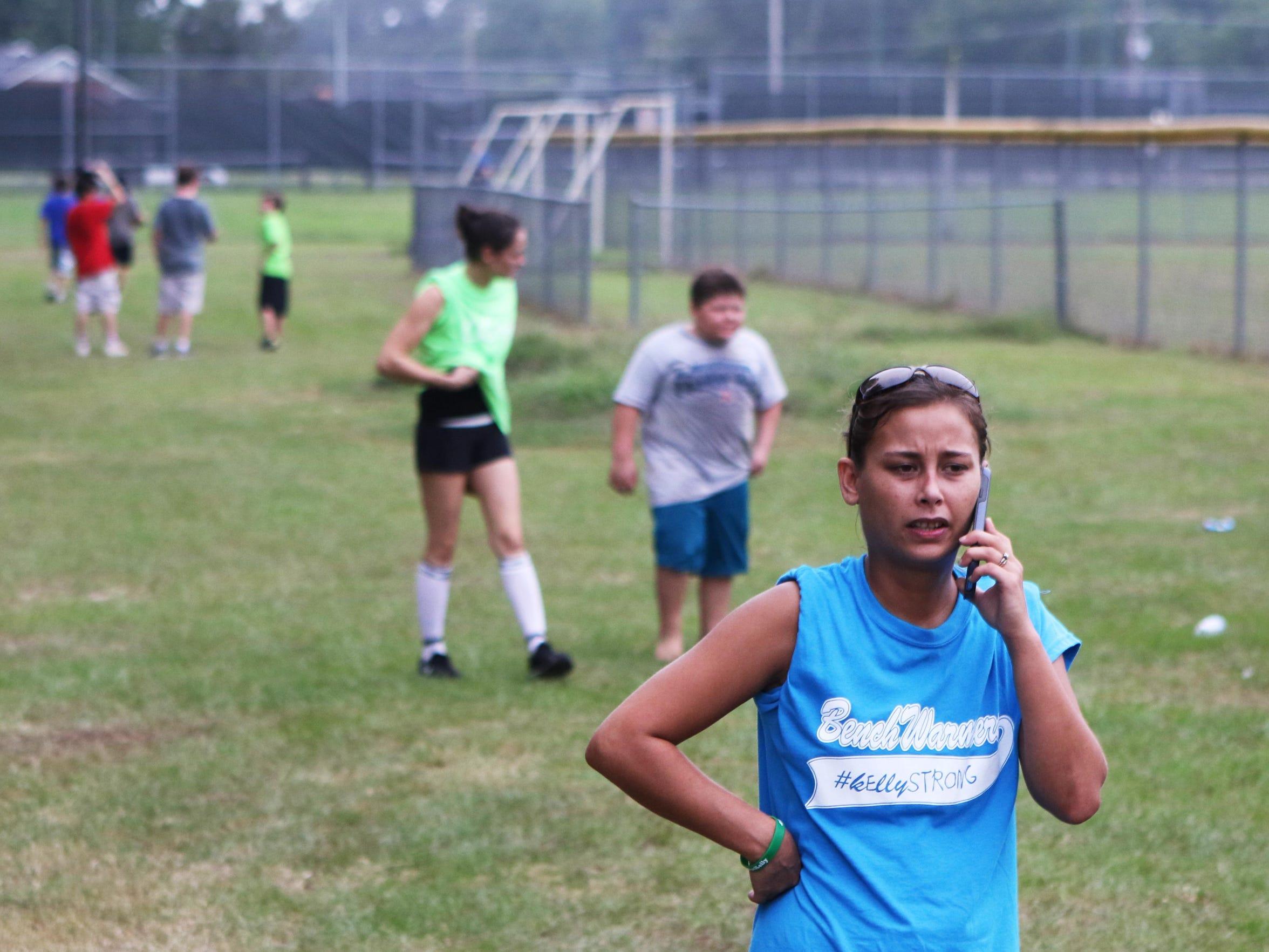 Shianne Graves talks on the phone as she runs a softball