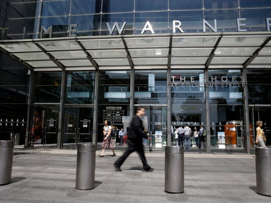 In this Tuesday, May 26, 2015 file photo, pedestrians walk by an entrance to the Time Warner Center in New York. On Saturday, Oct. 22, 2016, several reports citing unnamed sources said AT&T is in advanced talks to buy Time Warner, owner of the Warner Bros. movie studio as well as HBO and CNN. The giant phone company is said to be offering $80 billion or more, a massive deal that would shake up the media landscape.