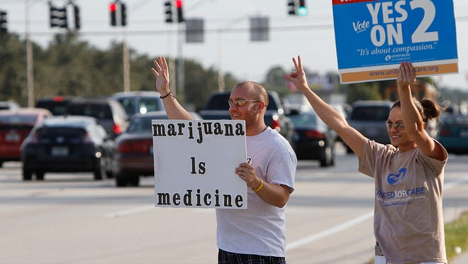 Ryan Kuhn, left, and girlfriend Michelle DeRhodes wave at honking supporters of  Amendment 2 on Tuesday along U.S. 41 in Fort Myers. Michelle found relief from her epileptic seizures while taking marijuana in Oregon.