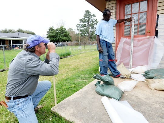 Emmett Wallace holds up a meter as Dale Rachal, who was hired by the city to check the elevation of water, takes measurements at a house in the Allendale.