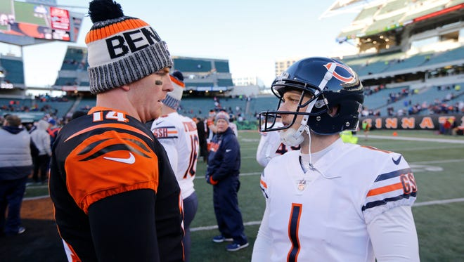 Cincinnati Bengals quarterback Andy Dalton (14) and former Bengals kicker Mike Nugent catch up the fourth quarter of the NFL Week 14 game between the Cincinnati Bengals and the Chicago Bears at Paul Brown Stadium in downtown Cincinnati on Sunday, Dec. 10, 2017. The Bengals fall to 5-8 with a 33-7 loss to the Bears.