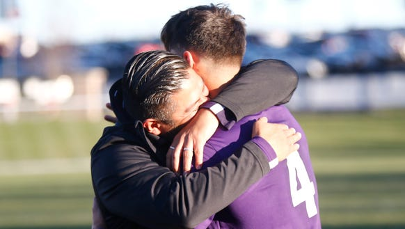 New Rochelle coach Jarohan Garcia hugs player Marcos