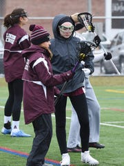 Jaclyn Murphy, left, head coach for Arlington's JV girls lacrosse team, demonstrates a technique for Emma Newman, right, before Saturday's opening game at home against Monroe-Woodbury.