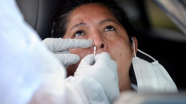Sara Salazar, of Framingham, receives a free, state-sponsored COVID-19 nasal swab test Wednesday from her car in the parking lot of the Joseph P. Keefe Technical High School.