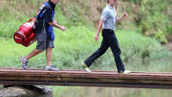 Rory McIlroy and his caddie, J.P. Fitzgerald, walk across a bridge after teeing off the ninth hole Friday at the PGA Championship at Valhalla.