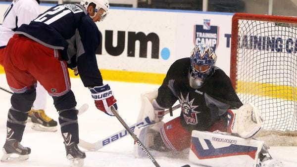 The Rangers' Derek Stepan, left, tries to get a shot past goalie Henrik Lundqvist during a drill on the first day of training camp at the Rangers' training facility in Greenburgh Sept. 19, 2014.