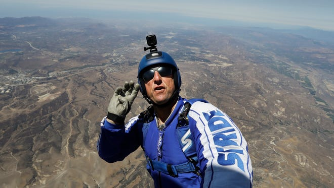 In this Monday, July 25, 2016 photo, skydiver Luke Aikins signals to pilot Aaron Fitzgerald as he prepares to jump from a helicopter in Simi Valley, Calif. After months of training, this elite skydiver says he's ready to leave his chute in the plane when he bails out 25,000 feet over Simi Valley on Saturday. That's right, no parachute, no wingsuit and no fellow skydiver with an extra one to hand him in mid-air.