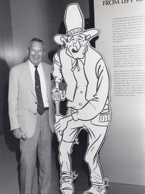 Jack Jurden poses with his cartoon of President Lyndon B. Johnson while it was on display at the U.S. National Archives in Washington.