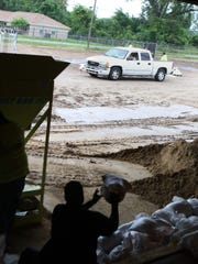 Public Works employees fill and load sandbags into