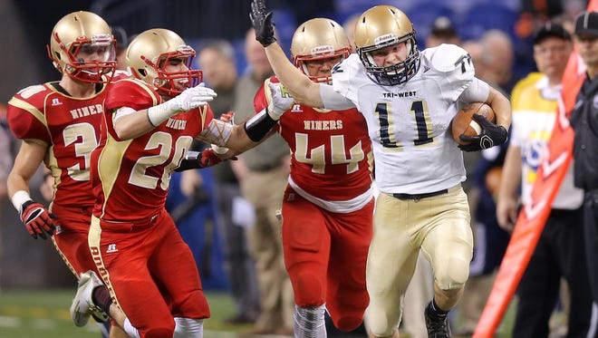 Tri-West wide receiver Wesley Cook tries to stiff-arm Andrean defensive back John Albomonte after breaking off for a 63-yard run in the first half of the IHSAA 3A State Football Finals held at Lucas Oil Stadium on Saturday, Nov. 29, 2014. The score was tied 21-21 at halftime.