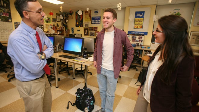 Charles Gulian from Ossining High School chats with science research teachers Angelo Piccirillo and Valerie Holmes after Gulian was named an Intel Science Talent Search finalist Wednesday.