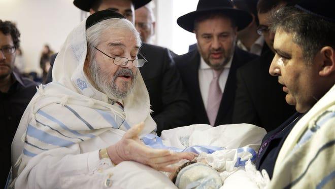 In this Feb. 11, 2015 photo, Abraham Romi Cohn, left, performs the bris, or ritual circumcision, of Yosef Sananas in New York.