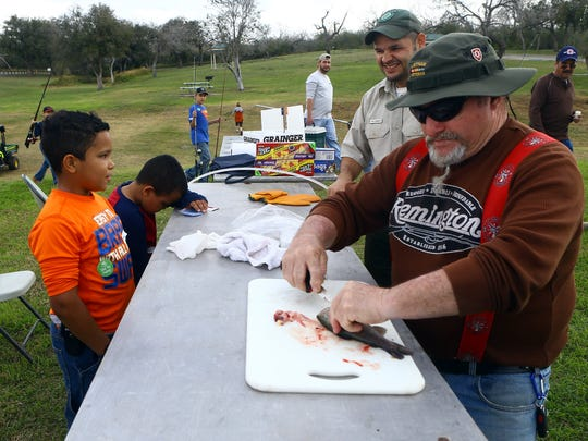 Volunteer Larry Coleman, right, cuts and cleans up a rainbow trout for William Lester, 10, left, after catching it during the 23rd Annual Kid Fish event Saturday Jan. 31, 2015 at Lake Corpus Christi State Park in Mathis.