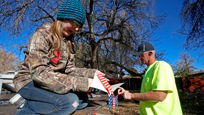 At left, Tammy Vandruff and Jason Mobley, both of Aztec, get their float ready on Saturday during the Veterans Day parade on Main Avenue in Aztec.