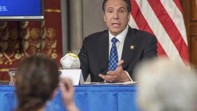 Gov. Andrew Cuomo addresses the media while holding an n95 mask during his daily press briefing on Friday.