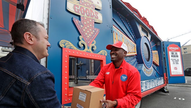 In this May 24, 2018, photo Amazon worker Khayyam Kain, right, hands off a package to a customer at an Amazon Treasure Truck in Seattle. The Treasure Truck is a quirky way for the online retailer to connect with shoppers in person, expand its physical presence and promote itself. Amazon has also used the trucks to try to bring people into Whole Foods, the grocery chain it bought last year. The trucks debuted two years ago and now roam nearly dozens of cities in the United States and England.