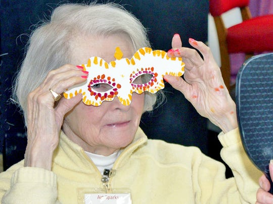 Anita Anderson tries on a mask she created in Art Sparks, an art program designed for people with memory loss and their care providers at the Paramount Center for the Arts earlier this year.