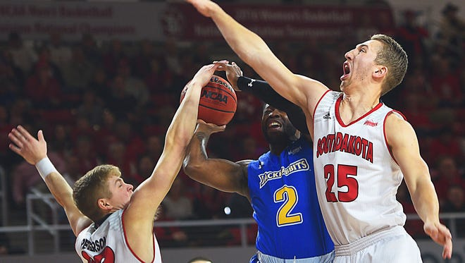 SDSU's Tevin King attempts to score past USD's Tyler Peterson, left, and Tyler Hagedorn, right, during the game Wednesday, Jan. 24, in Vermillion.