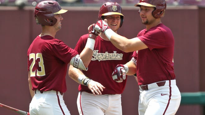 FSU's Cal Raleigh is congratulated by Reese Albert, left, and Rhett Aplin, center, after hitting a home run in the first game of their doubleheader against Mount St. Mary's at Dick Howser Stadium on Saturday, May 12, 2018.