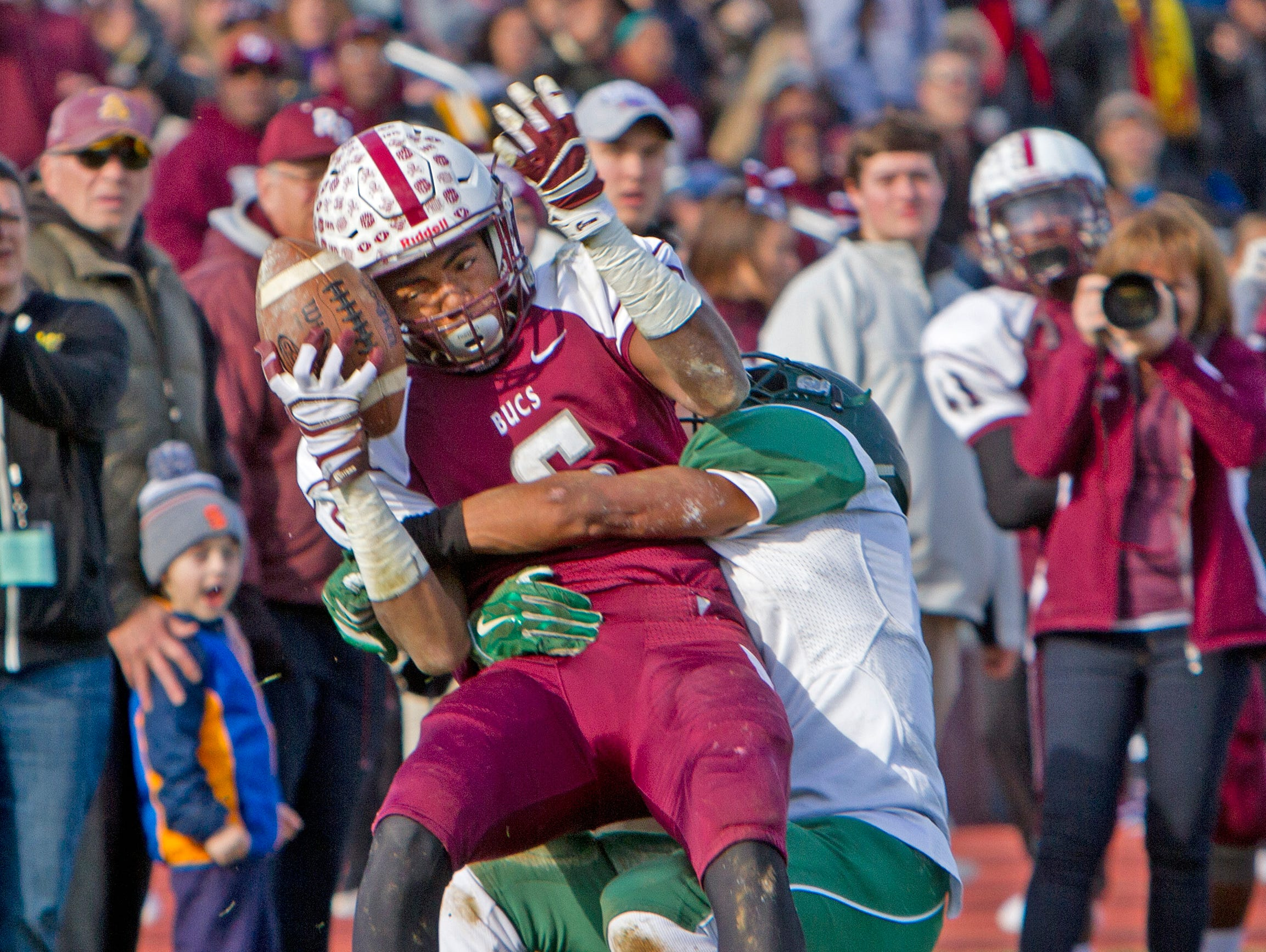 Red Bank Regional's Sadiq Palmer pushes the ball against his helmut after catching it to secure a pass that set up his team's first touchdown. Long Branch vs Red Bank Regional Thanksgiving Day Football game in Red Bank NJ on November 26, 2015.