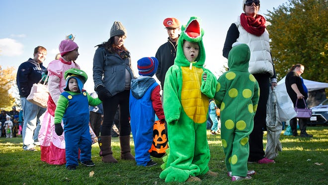 Children wait their turn in line for one of the many activities during Friday's Pumpkinfest event at Lake George in St. Cloud.