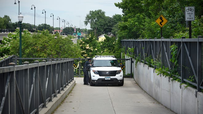 A St. Cloud police squad car blocks an entrance to the RiverWalk trail near the Granite City Crossing Bridge Thursday, June 22, in St. Cloud. A male body was found on the banks of the Mississippi River in the area.