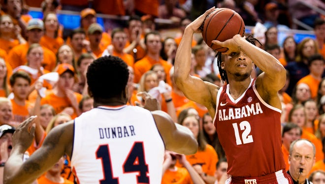 Alabama Crimson Tide guard Dazon Ingram (12) shoots as Auburn Tigers guard Malik Dunbar (14) guards him during the NCAA basketball game on Wednesday, Feb. 21, 2018, in Auburn, Ala.