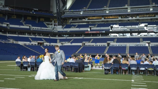 Jeni and Kevin Bubb walk away from their friends and family as newlyweds, during a wedding at Lucas Oil Stadium, Indianapolis, Saturday, July 11, 2015. The stadium charges people for different amenities like catered receptions, seating, and air conditioning.