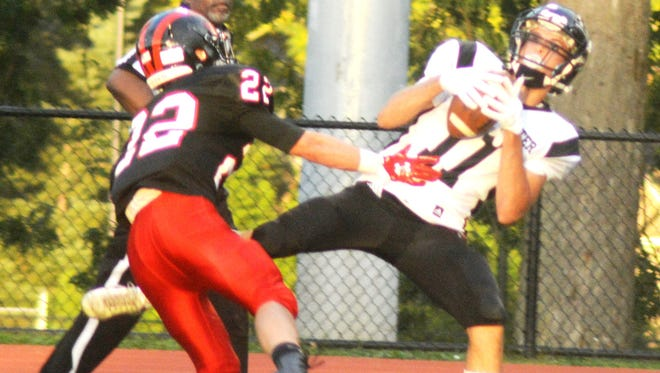 Manchester receiver Kristian Kaca (11) making a catch as Glen Rock's Ashton Dalessio defends.