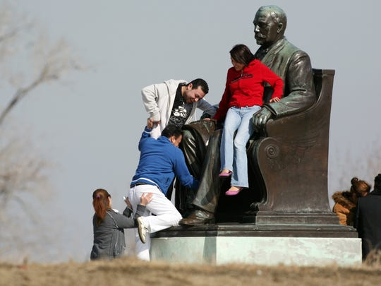 James Scott doesn't seem to mind as people climb all over his likeness at Belle Isle in Detroit.