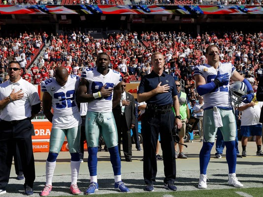 Dallas Cowboys defensive back Orlando Scandrick (32), wide receiver Dez Bryant (88), head coach Jason Garrett, center right, and tight end Jason Witten (82) stand during the performance of the national anthem before an NFL football game against the San Francisco 49ers in Santa Clara, Calif., Sunday, Oct. 22, 2017. (AP Photo/Marcio Jose Sanchez)