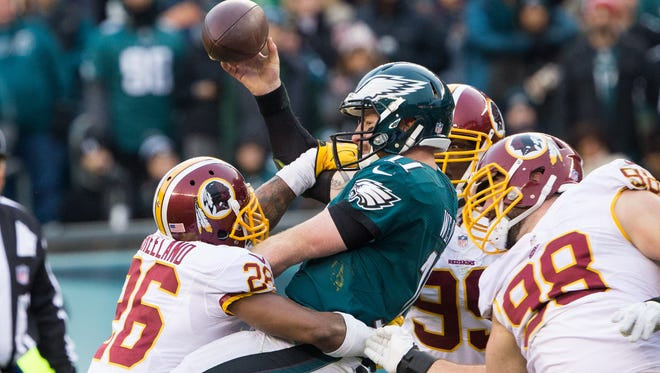Eagles quarterback Carson Wentz (11) fumbles the ball as he is hit by Redskins cornerback Bashaud Breeland (26) and defensive tackle Matthew Ioannidis (98) during a 27-22 loss on Sunday.