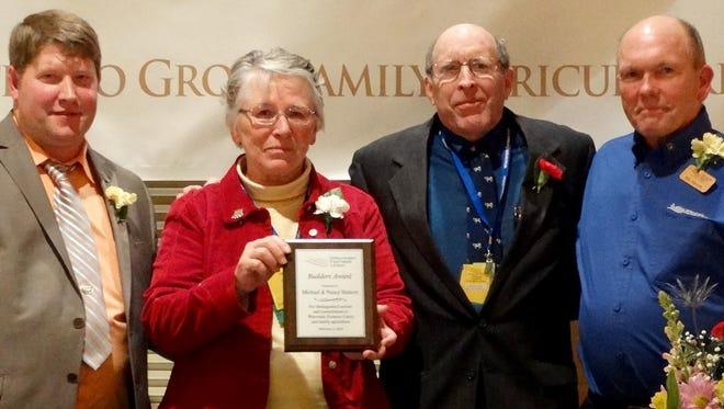 Wisconsin Farmers Union President Darin Von Ruden, left, and board member Rick Adamski, right, present a Builders Award to Michael and Nancy Slattery of Maribel.