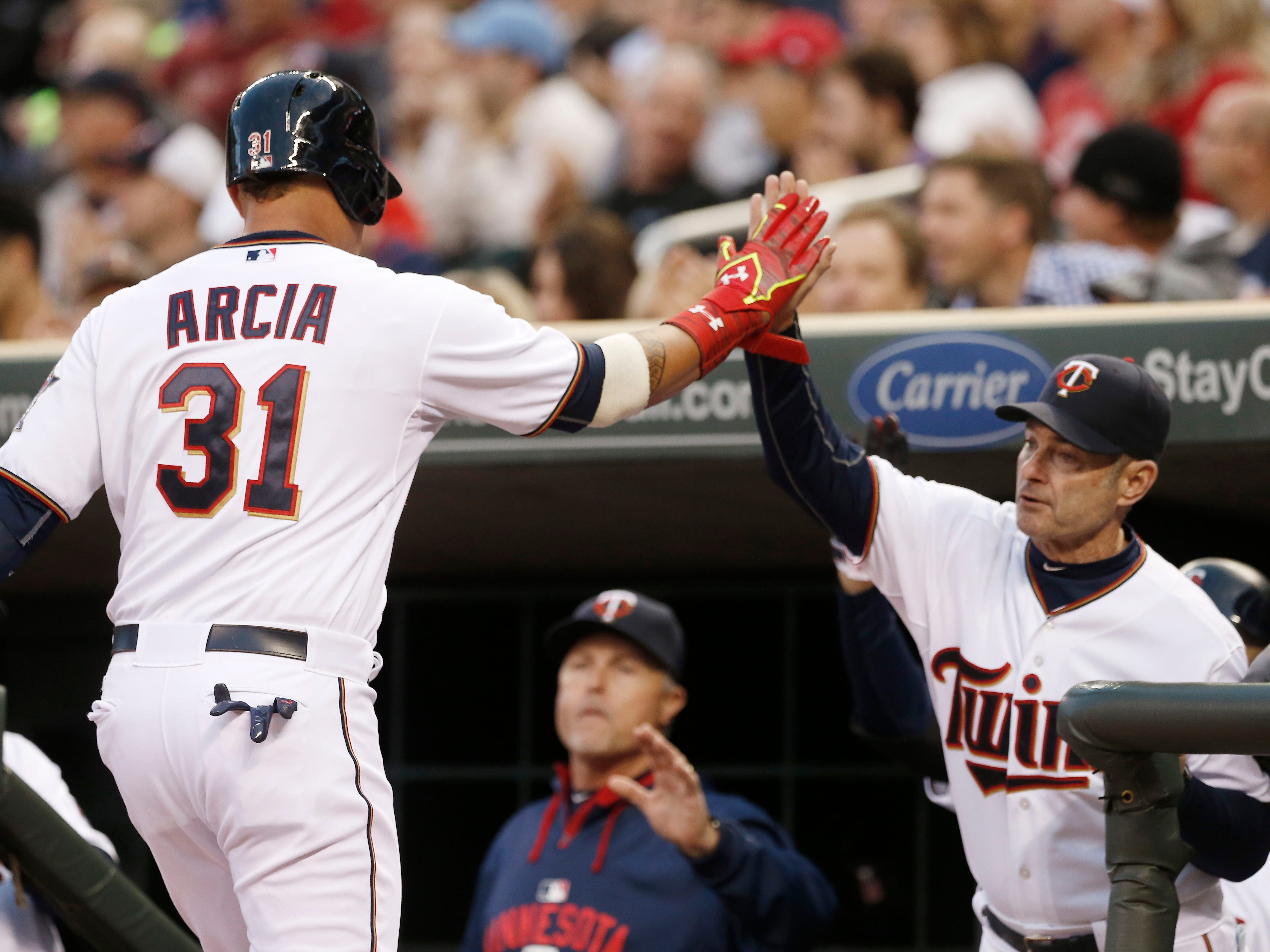 Minnesota Twins manager Paul Molitor, right, congratulates Oswaldo Arcia as he scores on a single by Danny Santana off Detroit Tigers starting pitcher Anibal Sanchez in the third inning of a baseball game, Tuesday, April 28, 2015, in Minneapolis. (AP Photo/Jim Mone)