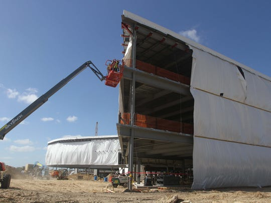 A welder works on a crane as construction continued on the new headquarters for the Hertz Corp. being built in Estero.