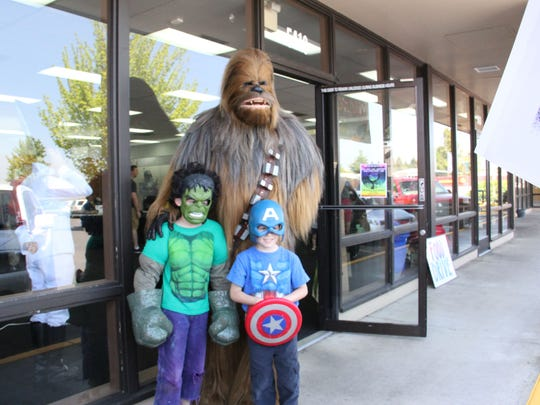 Cole, 8, and Brandon, 6, Layman pose for a picture with Chewbacca at Free Comic Book day on Saturday at Tony's Kingdom of Comic & Collectibles.