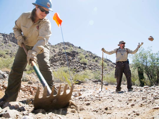 Crew Leader Valerie Seeton, in front, works with a Glendale Community College student at the Maricopa Trail as part of the Conservation Corp program at the Estrella Mountain Regional Park on April 27, 2015.