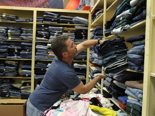 Harry Arnold, owner of Jam Apparel, located in Airport Plaza on Route 36 in Hazlet, arranges inventory in the store, which will be closing at the end of the month.