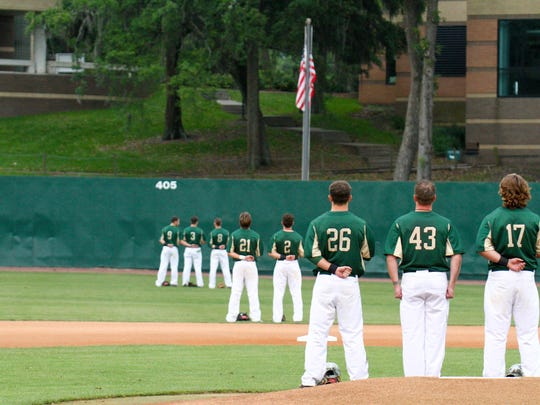 Starting pitcher Brian Holcomb (43) and his Jacksonville University teammates stand at attention for the national anthem before their game against Georgia Southern on April 28 in Jacksonville. It was the first college game for Holcomb, a 1998 Mason High graduate who is a member of the Wounded Warrior Project and an active duty Navy corpsman.